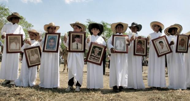 Niños de Las Brisas muestran fotos de sus familiares asesinados por los paramilitares. Foto por José Luis Rodríguez.