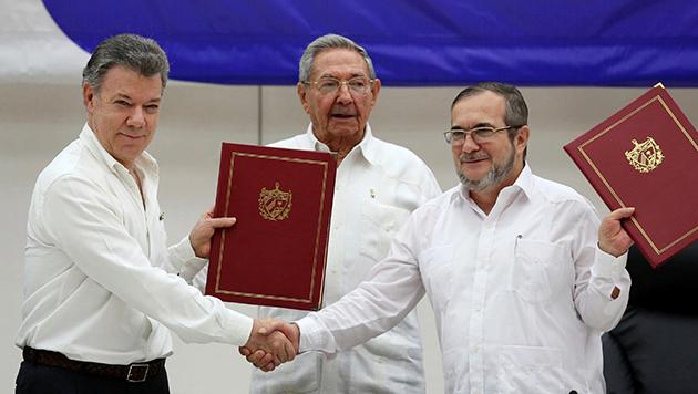 Foto: Portal Diario26/ Juan Manuel Santos y el comandante de FARC, Timoleón Jiménez. Además del presidente de Cuba, Raúl Castro.